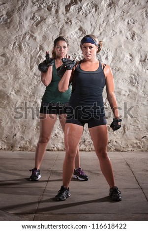 Pretty woman working out and sweating while lifting kettle bell weights - stock photo