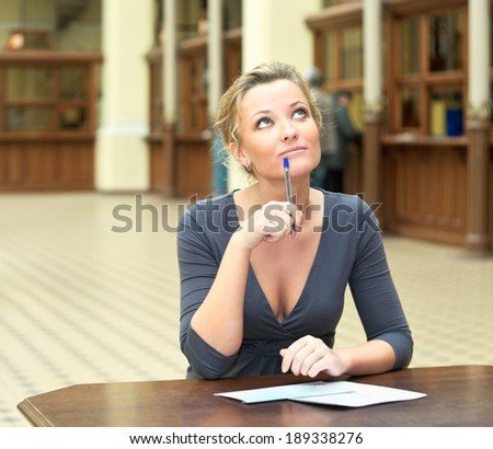 Pretty woman writing a letter and thinking - stock photo