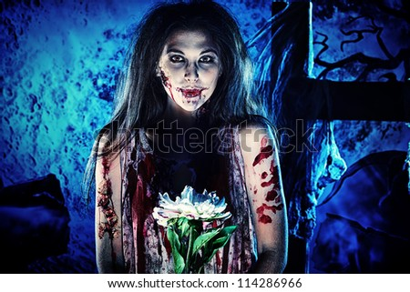 Pretty woman zombie standing at the night cemetery and tenderly holding a flower. - stock photo