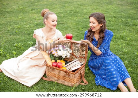 Pretty women are on a picnic. They are sitting on grass and smiling. The blond lady is taking an apple from the basket. The women are looking at it with joy - stock photo