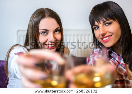 Pretty women having a drink together at home. - stock photo