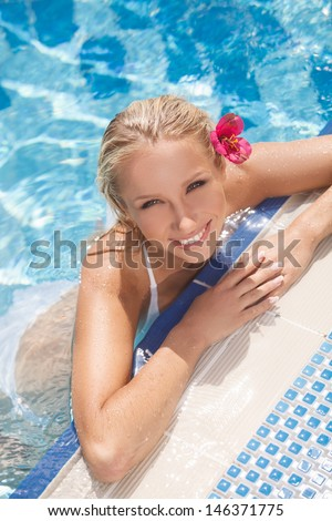 Pretty women in pool. Top view of attractive young women in bikini smiling at camera while standing in pool