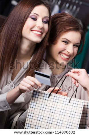 Pretty women pay for purchases with credit card - stock photo