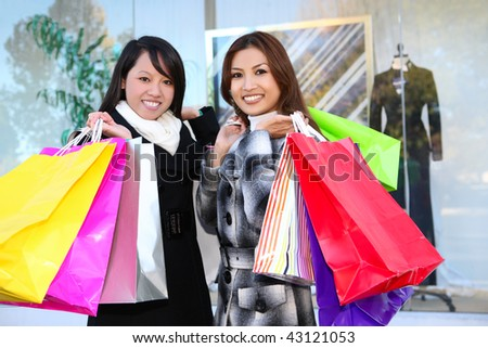 Pretty women shopping with colorful bags walking to the next store - stock photo