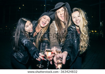 Pretty women toasting champagne glasses and having fun - Four girls drinking sparkling white wine and celebrate before going into club - stock photo