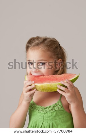 Pretty 5 year old girl eating watermelon wearing a green dress. - stock photo
