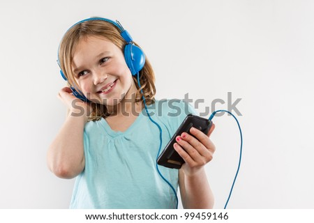 Pretty 8 year old little girl listening to blue headphones on her MP3 media player - stock photo
