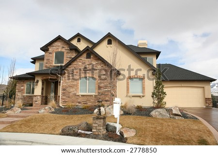 Pretty yellow stone house with blank for sale sign - stock photo