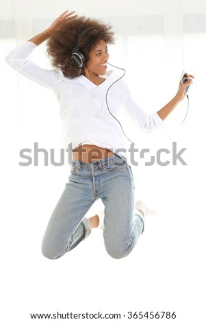 Pretty young african american girl listening music from her mobile phone and jumping. Standing against white background. - stock photo