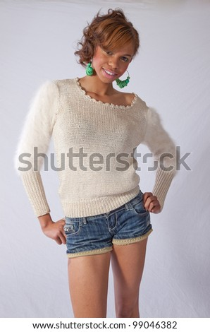 Pretty young African American woman in shorts and a white shirt, smiling with a thoughtful but friendly expression as she looked at the camera - stock photo