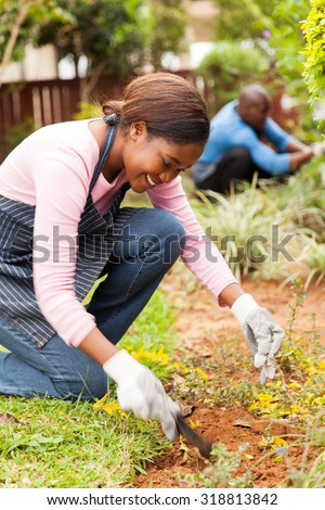 pretty young african girl gardening with her husband on background - stock photo