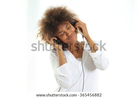 Pretty young afro american woman listening her favorite song.Standing against white background. - stock photo