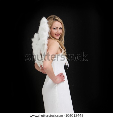 Pretty young angel in white visiting us on earth against a black background