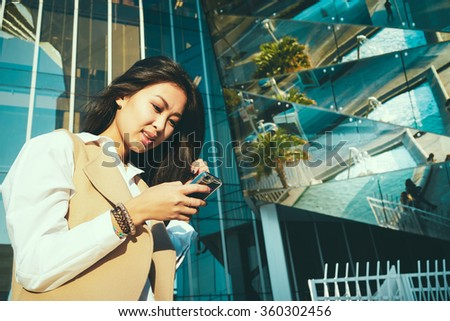 Pretty young Asian businesswoman uses modern smart-phone outside the office. portrait of a beautiful Asian female students recorded a video for her video blog - stock photo