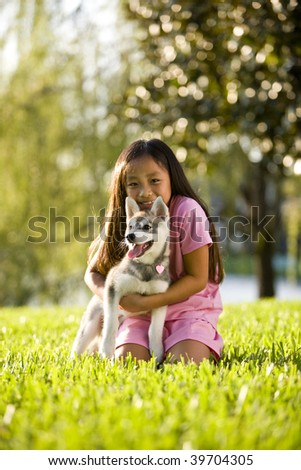 Pretty young Asian girl hugging Alaskan Klee Kai puppy sitting on grass - stock photo