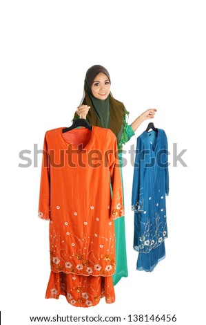 Pretty young Asian Muslim woman posses shopping with Baju Kurung action. Islamic fashionable attire concept - stock photo