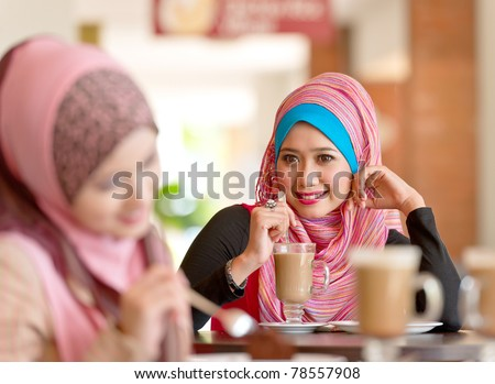 Pretty young Asian Muslim women having lunch at coffee shop