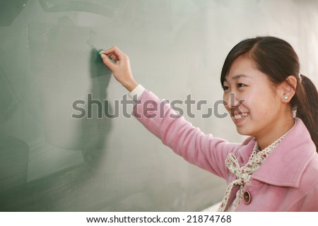 Pretty young asian teacher in front of a blackboard - stock photo