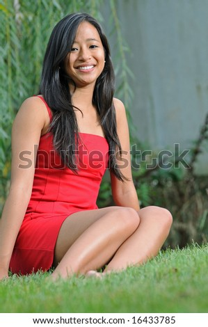 Pretty young Asian woman sitting in red dress smiling - stock photo