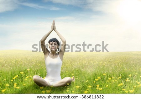 Pretty young Asian woman sitting on the green grass while meditating, shot on the meadow in springtime - stock photo