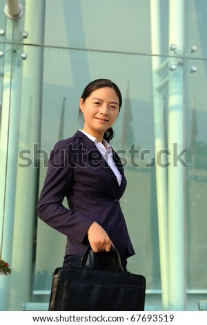 Pretty young  asian woman walking with laptop under the hand at office building - stock photo