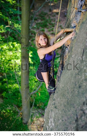 Pretty, young, athletic girl climbing on a rock wall with rope and carbines engaged. Summer time.