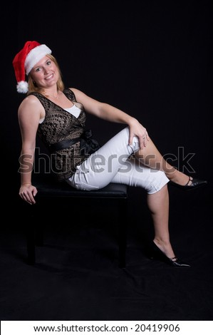 Pretty Young Blond German girl in Santa Hat over black background