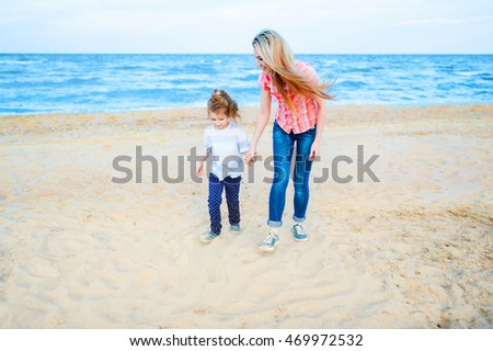 Pretty young blond mother with her little daughter walk along the sandy beach. Travel and Vacations.