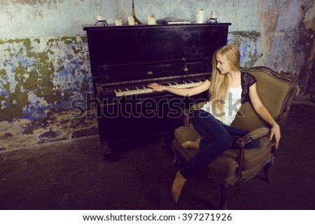 pretty young blond real girl at piano in old-style rusted interior, vintage concept - stock photo