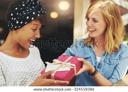 Pretty young blond woman giving an attractive young African American friend a surprise gift gift-wrapped with red paper, a bow and card - stock photo