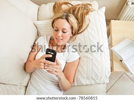 Pretty young blond woman lying on sofa and messaging with her smartphone