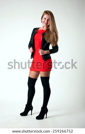 Pretty young blond woman model wearing tight short red dress, black leather jacket, black stockings, high heel shoes, standing, posing, looking at camera and smiling with toothy smile. Over gray - stock photo
