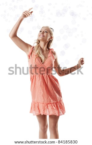 pretty young blond woman wearing a summer orange dress playing with some soap bubbles against white background - stock photo