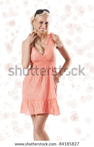 pretty young blond woman wearing a summer orange dress standing against white background with beautiful smile around some soap bubbles - stock photo