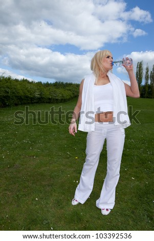 Pretty young blonde drinking water on a field - stock photo