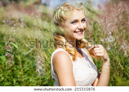 Pretty young blonde girl on blossoming field in a summer