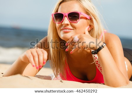 Pretty young blonde pretty girl at beach lying on sand. Woman wearing sunglasses have active time in summer. Summertime and lifestyle concept.