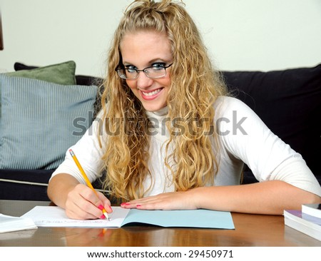 Pretty young blonde woman with blue exam book at home - stock photo
