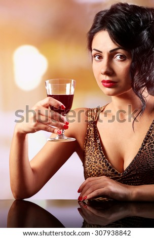 Pretty young brunet with wineglass on light blurred background