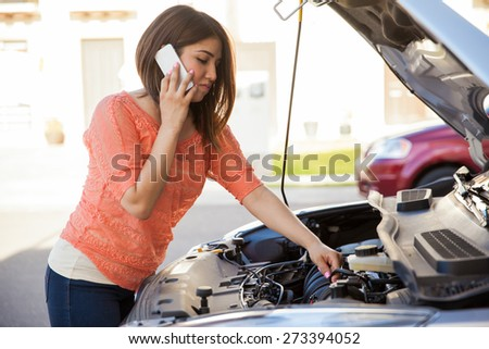 Pretty young brunette calling someone for help with her broken car - stock photo