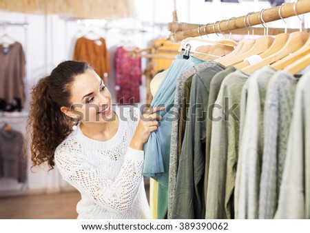 Pretty young brunette choosing new skirt on hangers in shop