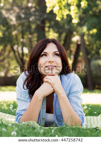 Pretty, young brunette dreaming in the park.