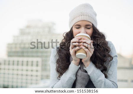 Pretty young brunette drinking coffee outside on a cloudy day - stock photo
