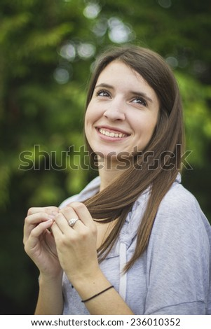 Pretty young brunette girl playing with her hair looking up and smiling. - stock photo