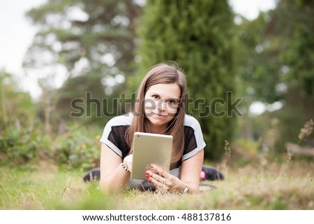 Pretty young brunette girl relaxing and using tablet in outside