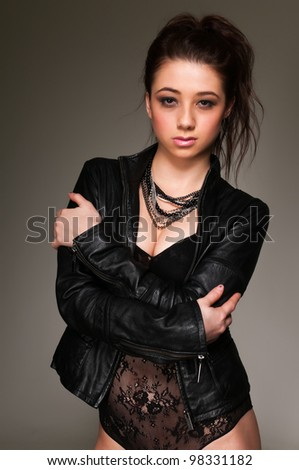 Pretty young brunette in a black leotard and leather jacket - stock photo