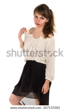 Pretty young brunette in a cream top and black skirt