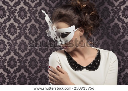 pretty young brunette in white elegant dress with a fashion mask ready for carnival party - stock photo