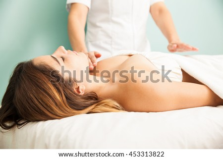 Pretty young brunette relaxing and receiving positive energy during a reiki therapy session at a spa - stock photo