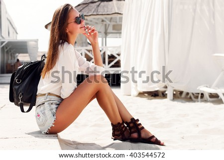Pretty young brunette sensual girl sitting in summer outdoor in sunglasses having fun on the beach in jeans shorts and backpack  - stock photo